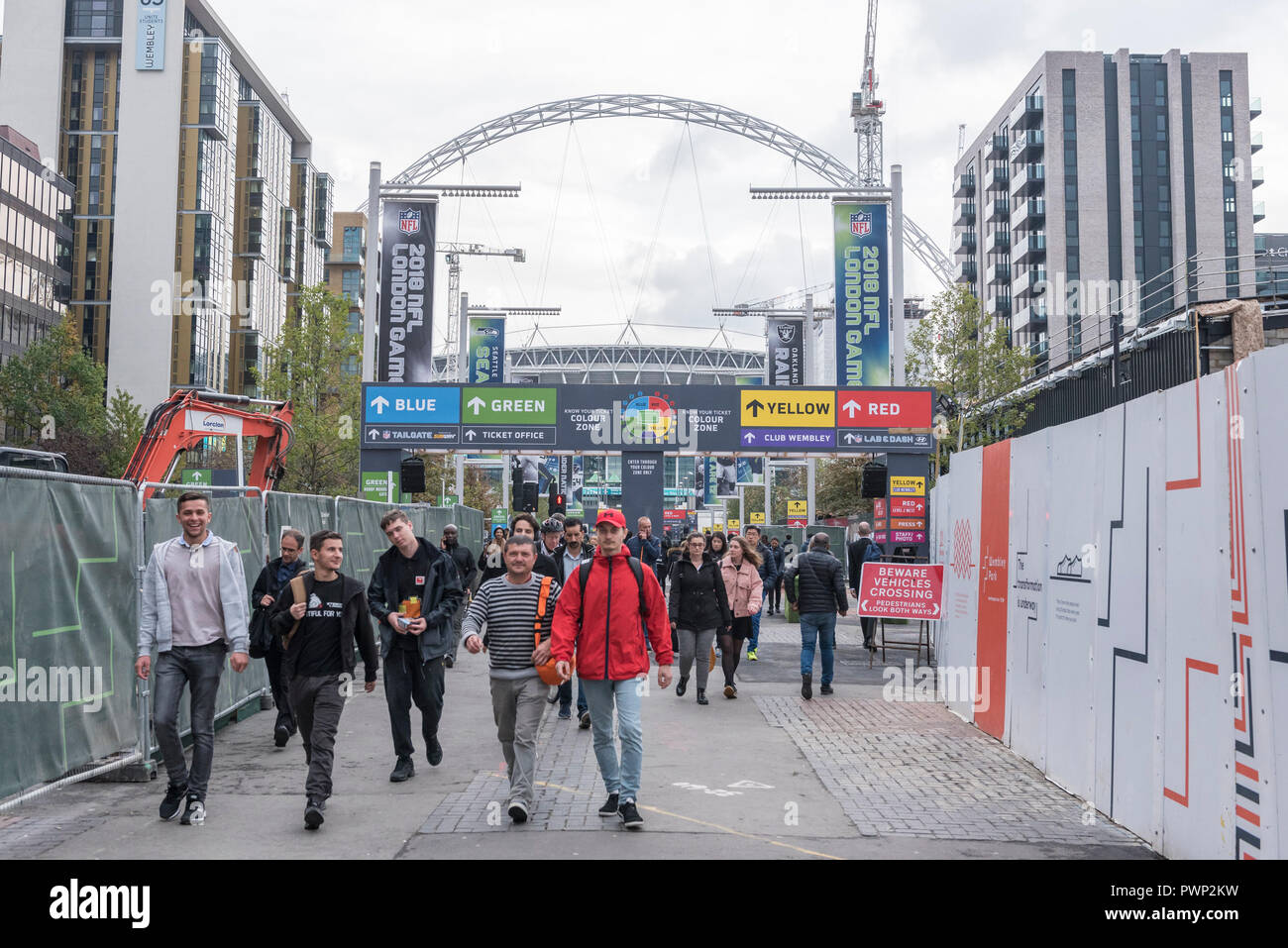 London, UK.  17 October 2018. Wembley Stadium in the distance as commuters walk down Olympic Way.  The area is currently decorated with NFL branding to promote the current three game series of NFL games at the stadium.  Shahid Khan, owner of Fulham FC and the Jacksonville Jaguars NFL team, has withdrawn his £600m offer to buy the stadium, amidst reports that he did not feel that he would receive sufficient support from The Football Association (FA).  The FA was due to vote on the potential sale on October 24.  Credit: Stephen Chung / Alamy Live News - Stock Image
