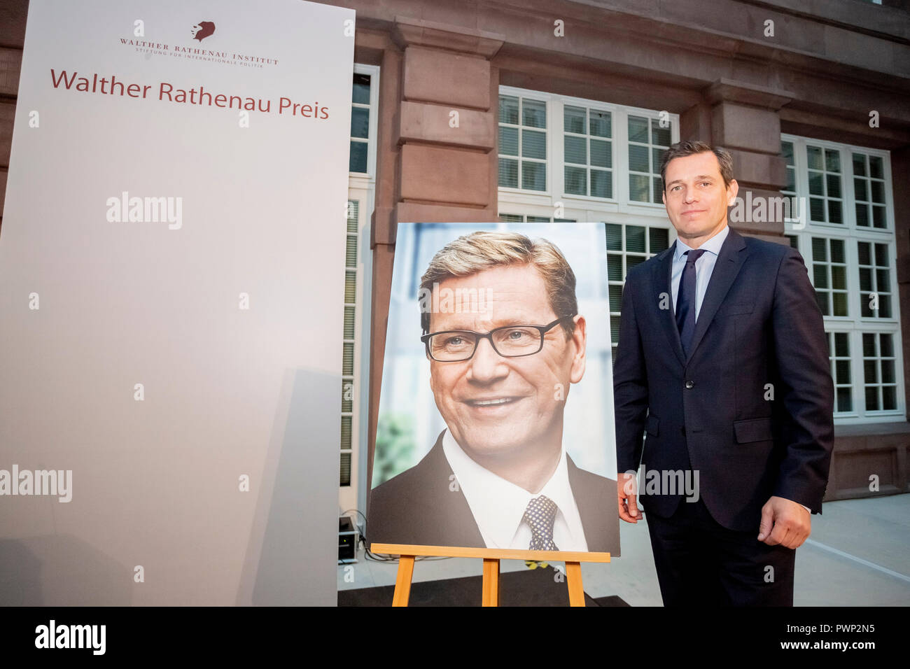 Berlin, Germany. 17th Oct, 2018. 17 October 2018, Germany, Berlin: Michael Mronz, life partner of the late Guido Westerwelle, stands next to a picture of Guido Westerwelle at the posthumous presentation of the Rathenau Prize 2018. Westerwelle is posthumously honoured by the Walther Rathenau Institute, Foundation for International Politics, 'for his work in the sense of a peaceful world order based on international understanding'. Credit: Christoph Soeder/dpa/Alamy Live News - Stock Image