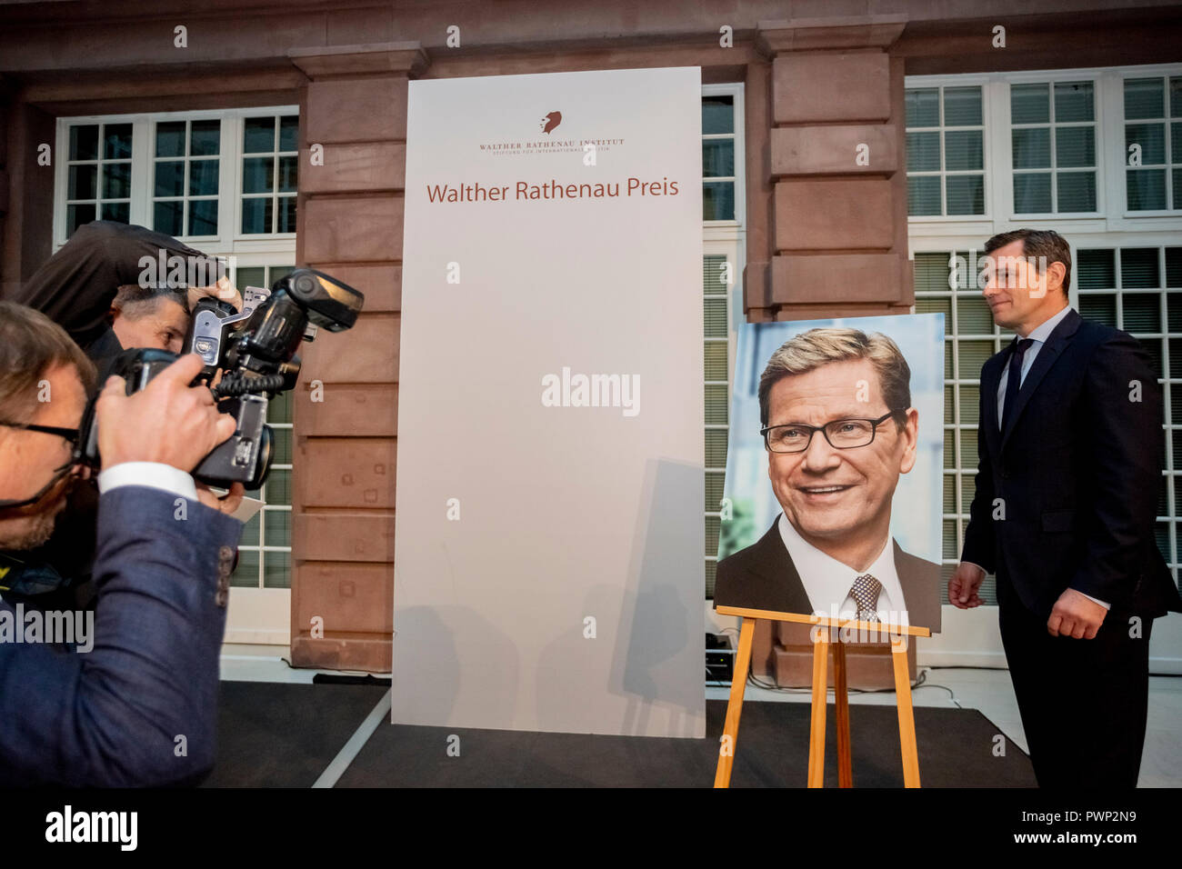Berlin, Germany. 17th Oct, 2018. 17 October 2018, Germany, Berlin: Michael Mronz, life partner of the late Guido Westerwelle, stands for photographers at the posthumous presentation of the Rathenau Prize 2018 next to a picture by Guido Westerwelle. Westerwelle is posthumously honoured by the Walther Rathenau Institute, Foundation for International Politics, 'for his work in the sense of a peaceful world order based on international understanding'. Credit: Christoph Soeder/dpa/Alamy Live News - Stock Image