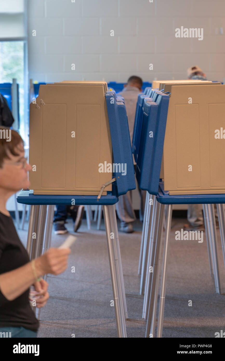 Raleigh, North Carolina, USA. 17th Oct, 2018.  Volunteer hands out 'I voted early' stickers to voters as they leave the polling place. Credit: Michael Reilly/Alamy Live News - Stock Image