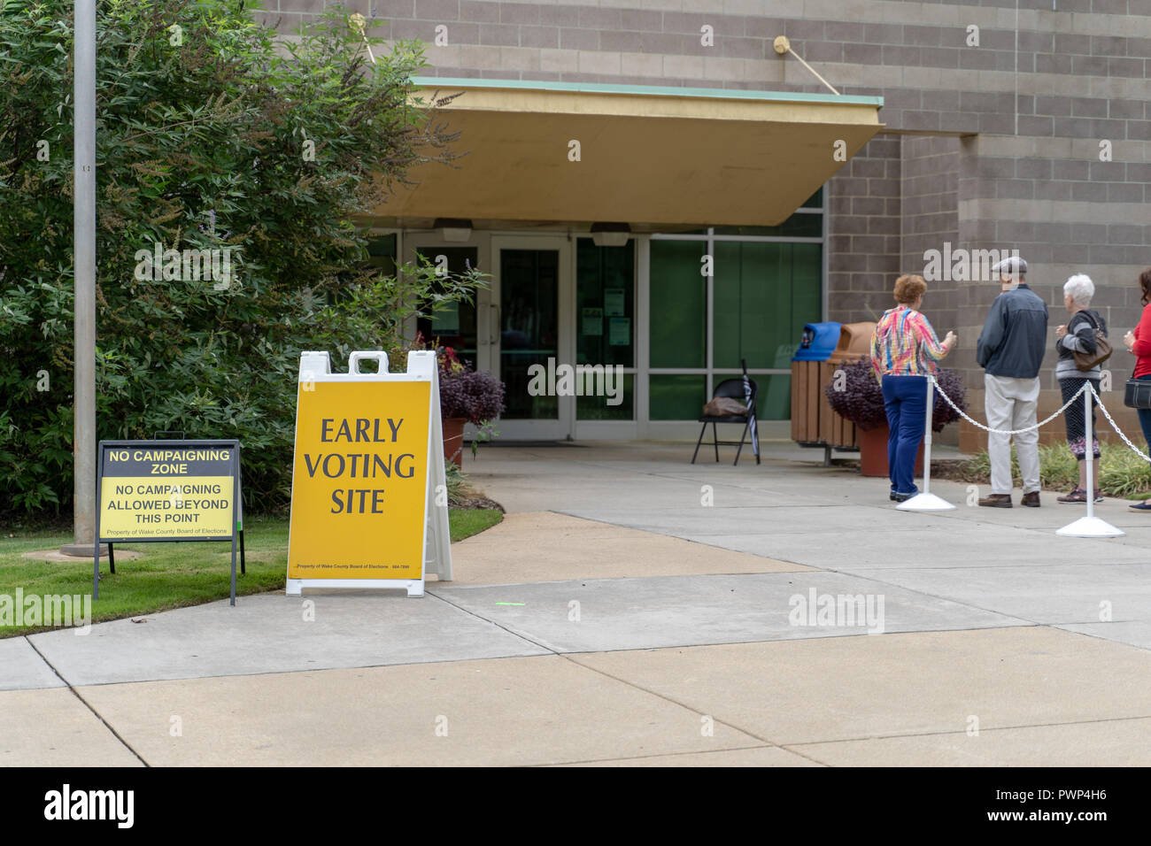 Raleigh, North Carolina, USA. 17th Oct, 2018.  Early voting begins for 2018 midterm elections, Lake Lynn Community Center. Early Voting Site sign seen with voters waiting in line to enter facility to cast ballot. Credit: Michael Reilly/Alamy Live News - Stock Image