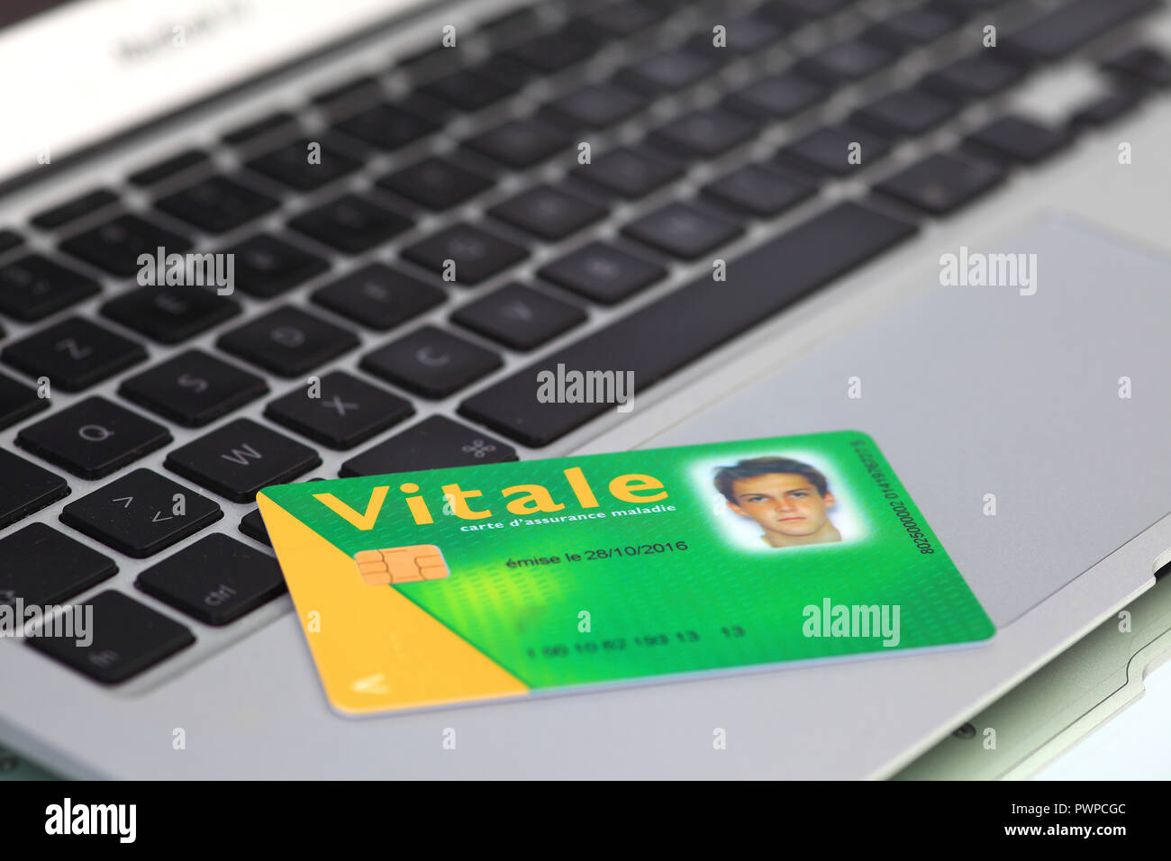 France. Young woman using smartphone by night.France, health card - Stock Image