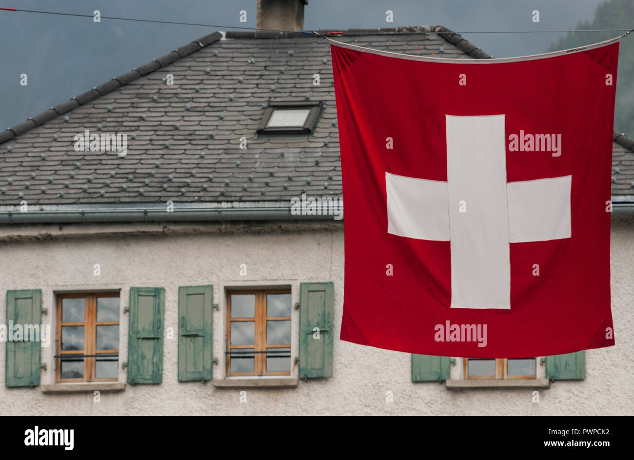 Switzerland, Valais canton, region of Sierre and Val d'Anniviers, village of Saint-Luc. Typical house and Swiss flag. Stock Photo