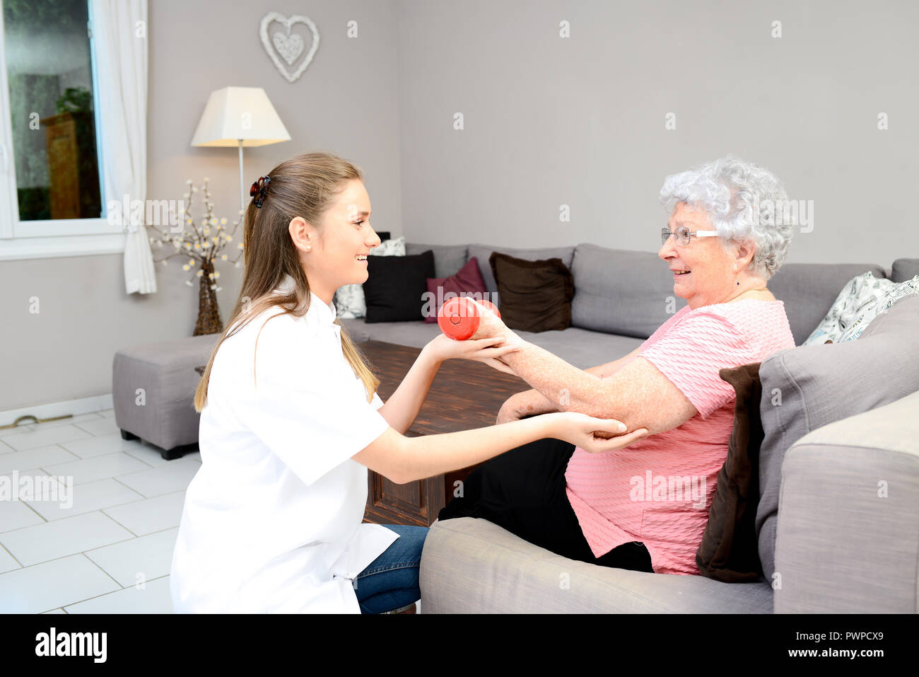 Young physiotherapist nurse helping elderly women physical rehabilitation at home - Stock Image