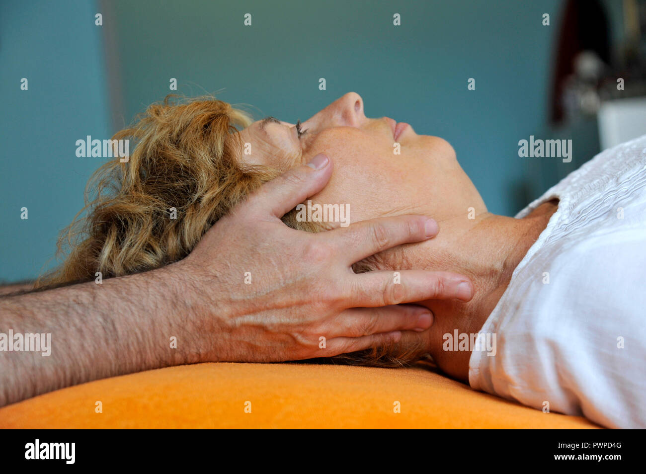 France, person in a osteopath's office, woman getting chiropractic treatment, face massage. - Stock Image