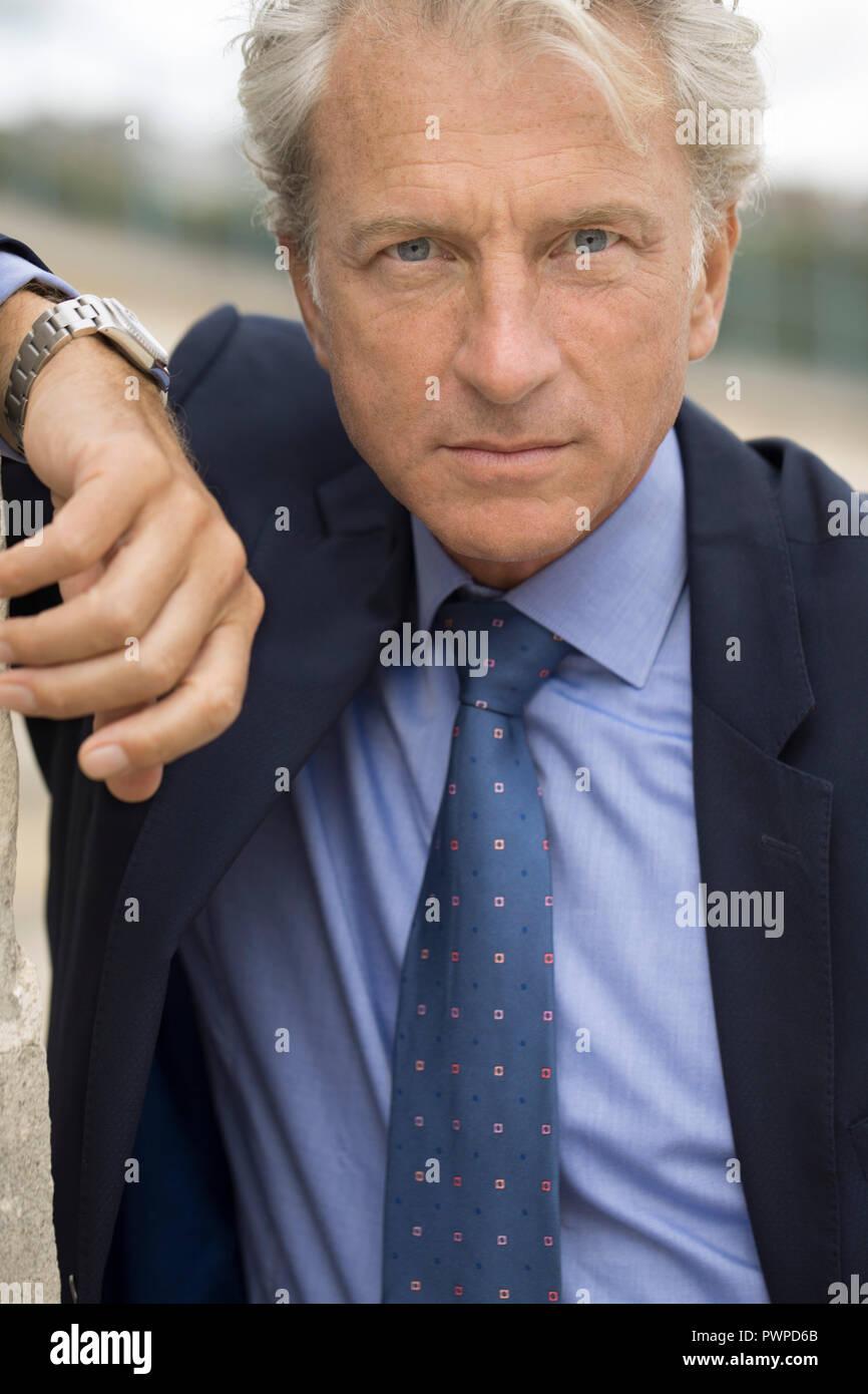 Homme sérieux d'âge mûr au regard intense en costume bleu appuyé contre un mur./Portrait of a serious mature man with intense eyes in blue suit leanin - Stock Image
