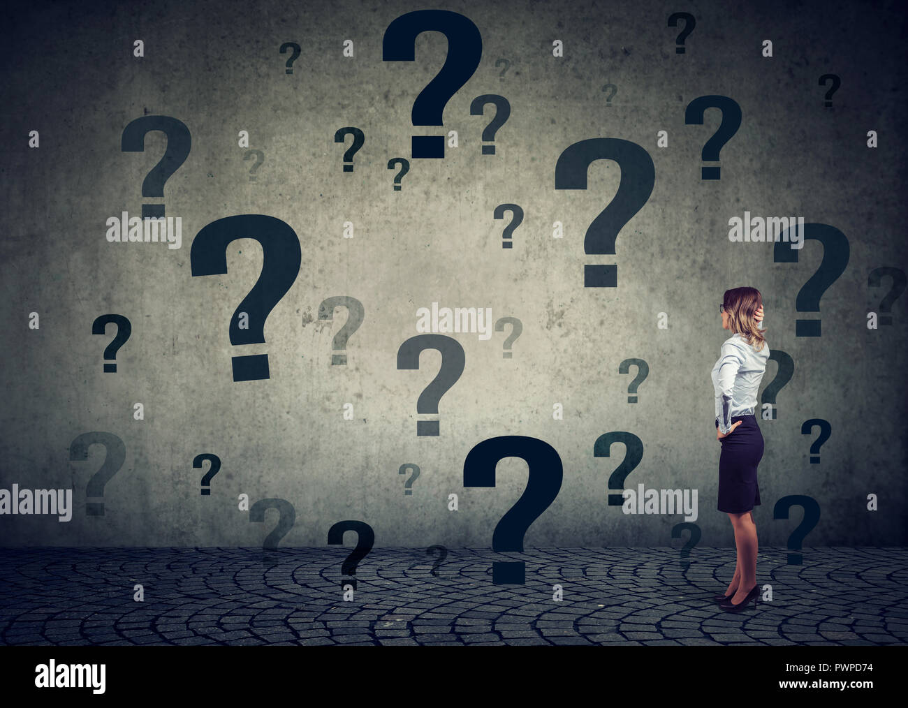 Rear view of young business woman with hand on head standing in front of a wall with many questions wondering what to do next. Businesswoman facing ch - Stock Image
