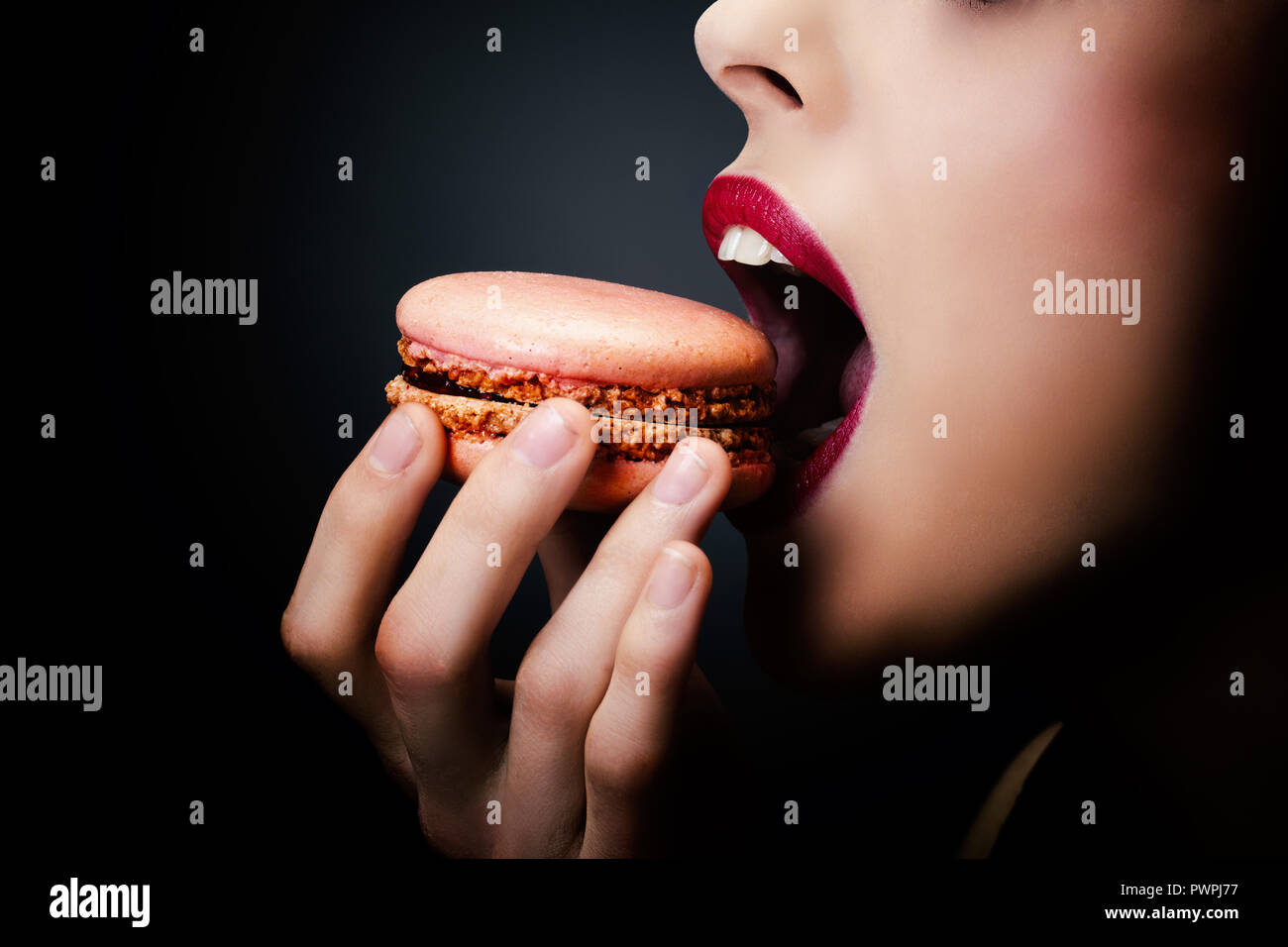 Tight shot of a girl enjoying a macaroon - Stock Image