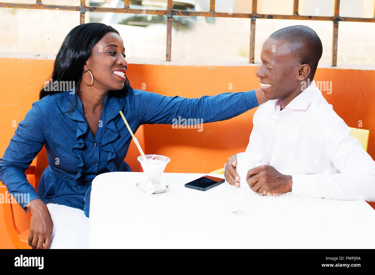 This couple is sitting in restaurant and friendly talk. - Stock Image