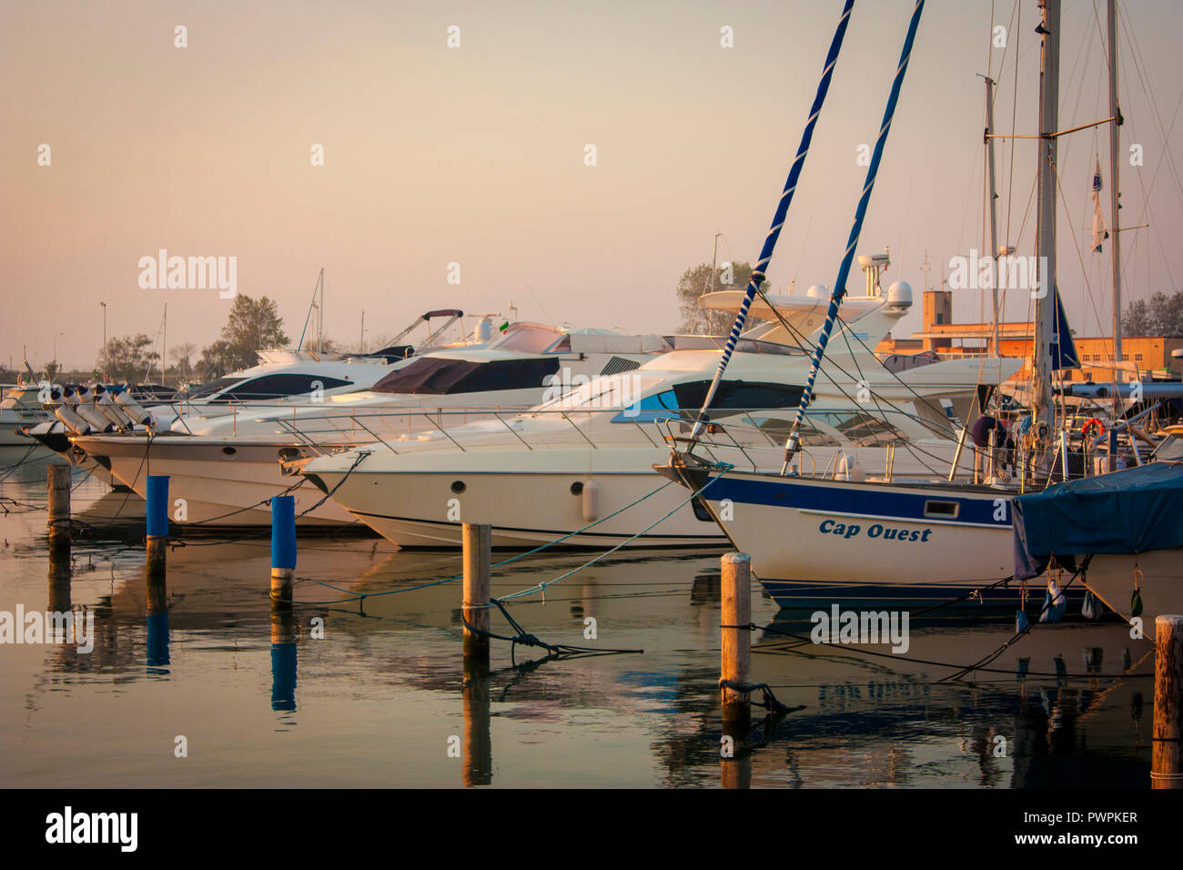 View of several boats moored on the great port of Albarella in Italy, illuminated by the warm colors of dawn - Stock Image