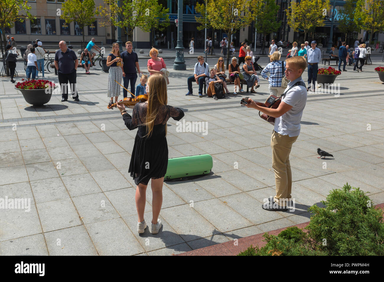Young people busking, two young buskers entertain passersby in Gedimino Prospektas in Vilnius, Lithuania. - Stock Image