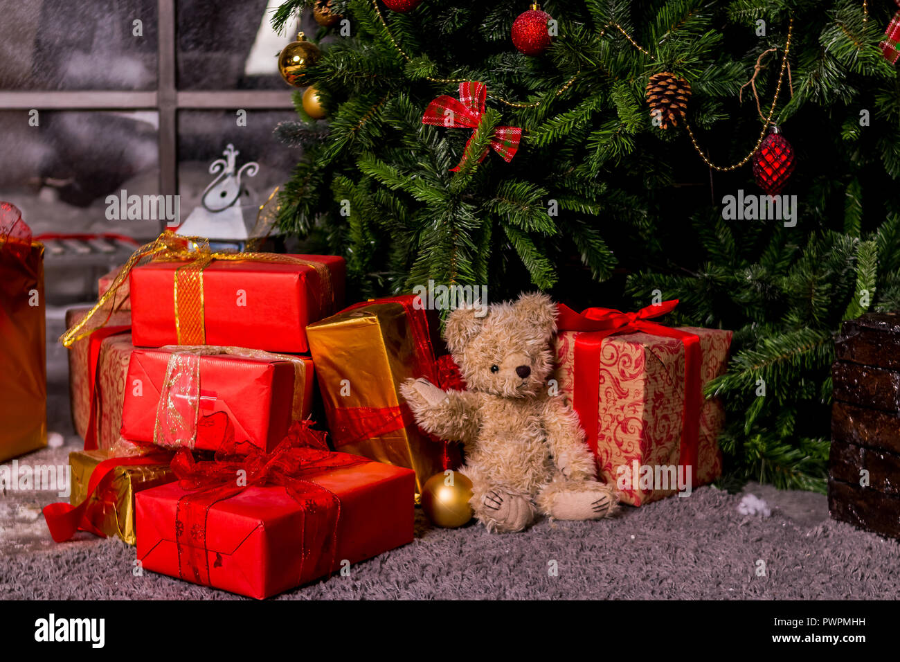 gifts under the Christmas tree, toy bear and boxes, the concept of a ...