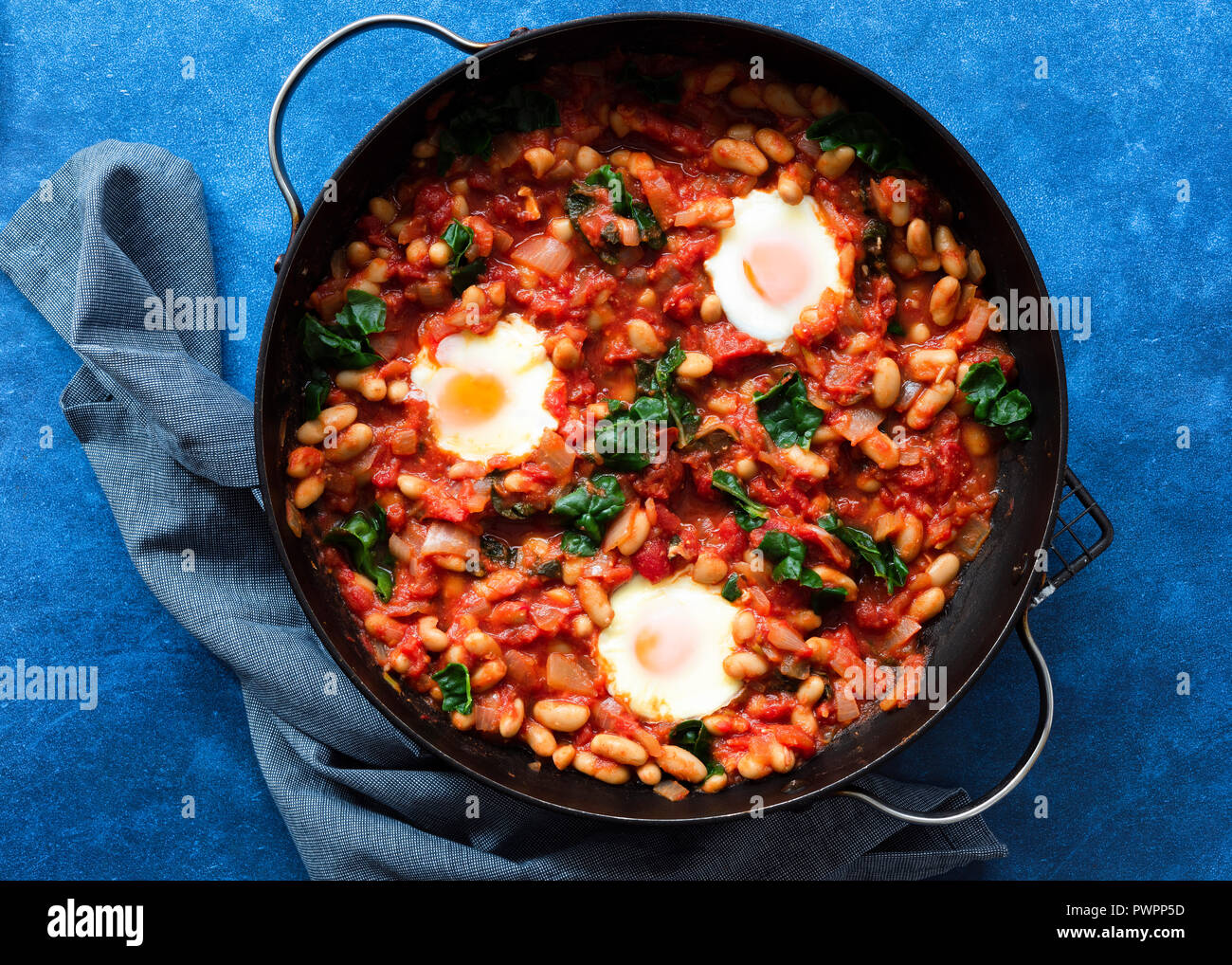 Shakshuka with silverbeet in a pan. - Stock Image