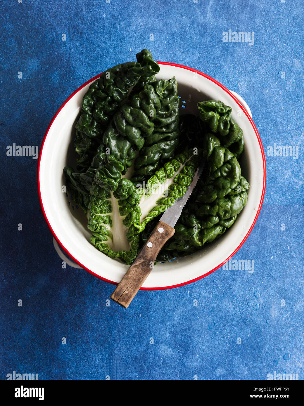 Silverbeet leaves in a colander with a knife. - Stock Image