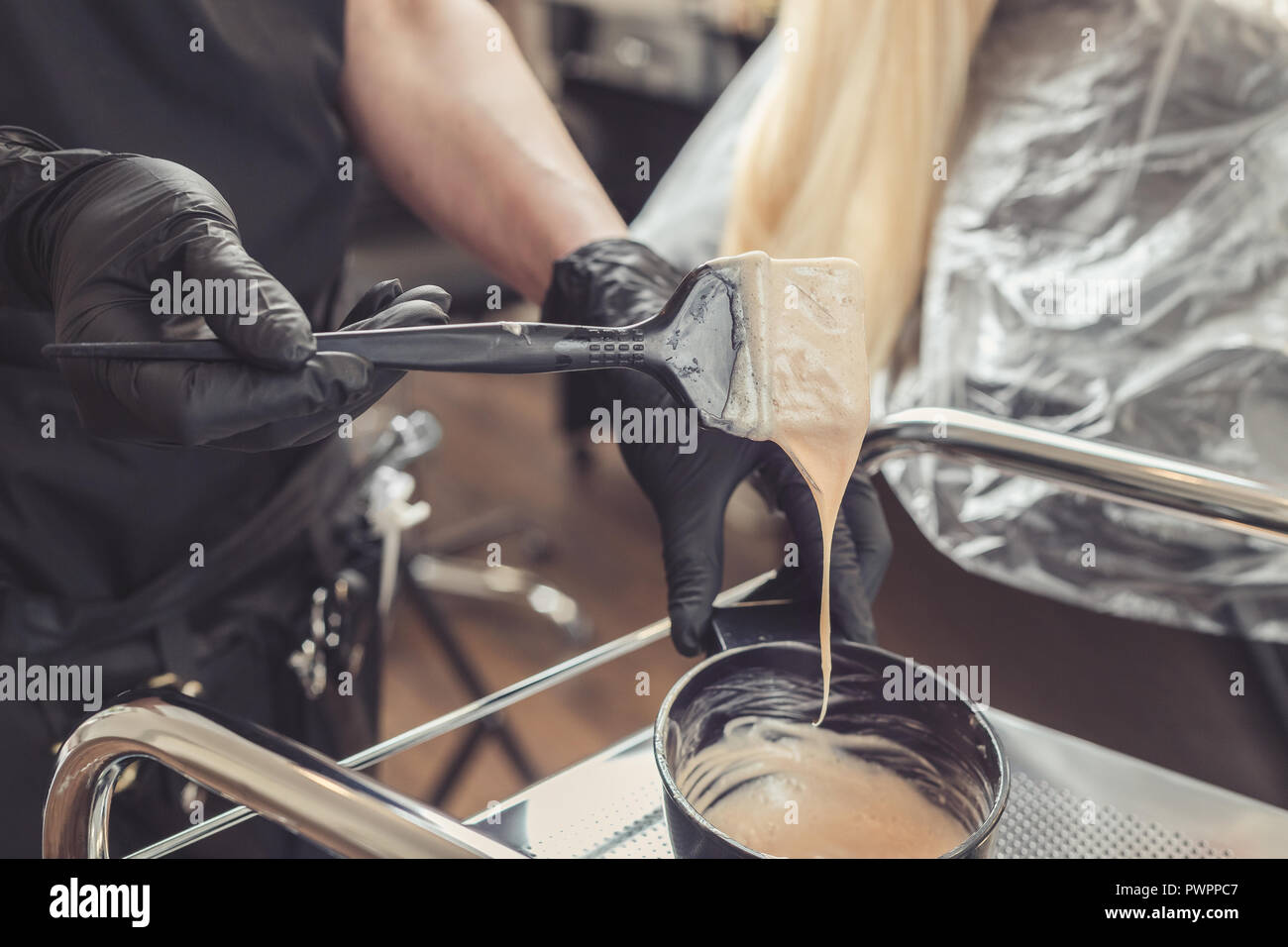 Stylist preparing a hair dye in a container, hairdresser salon concept - Stock Image