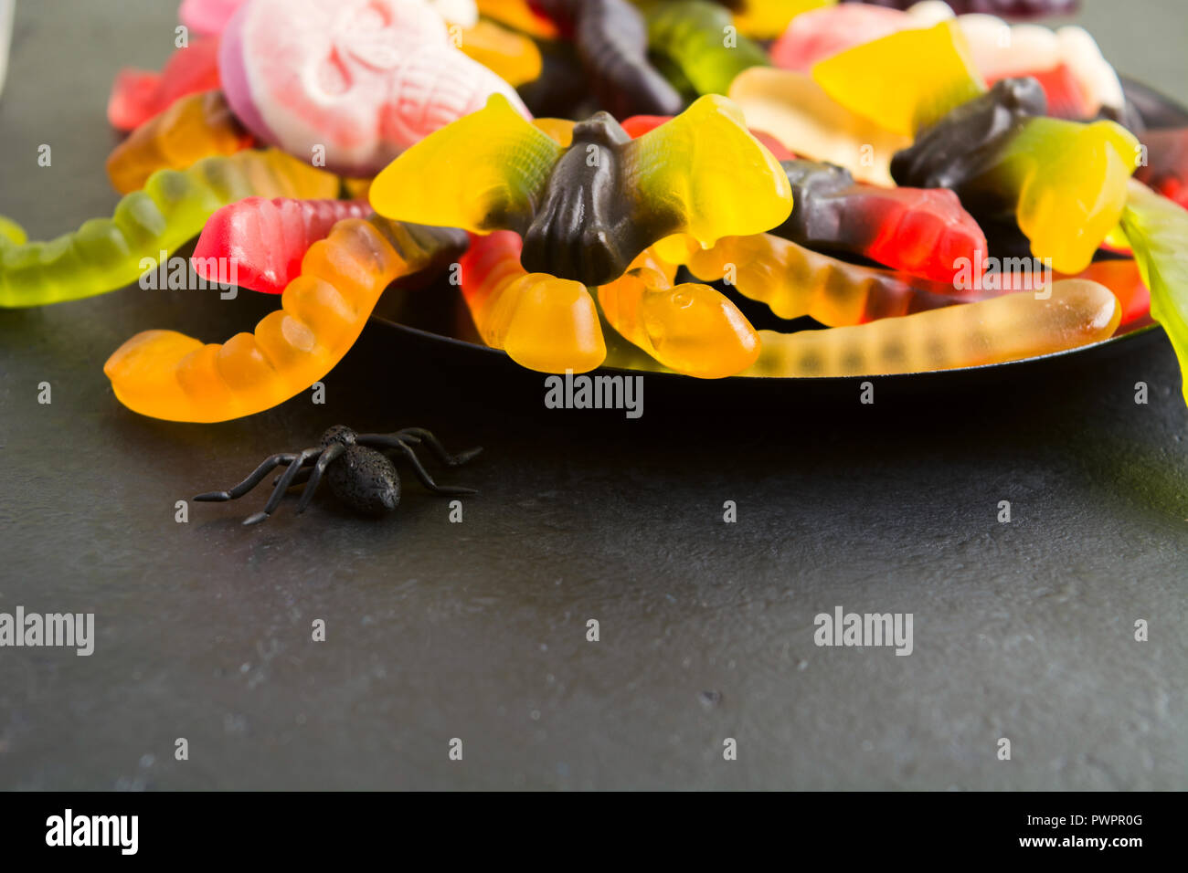 Plate of various Halloween candies and spider on black backgroundwith copy space - Stock Image