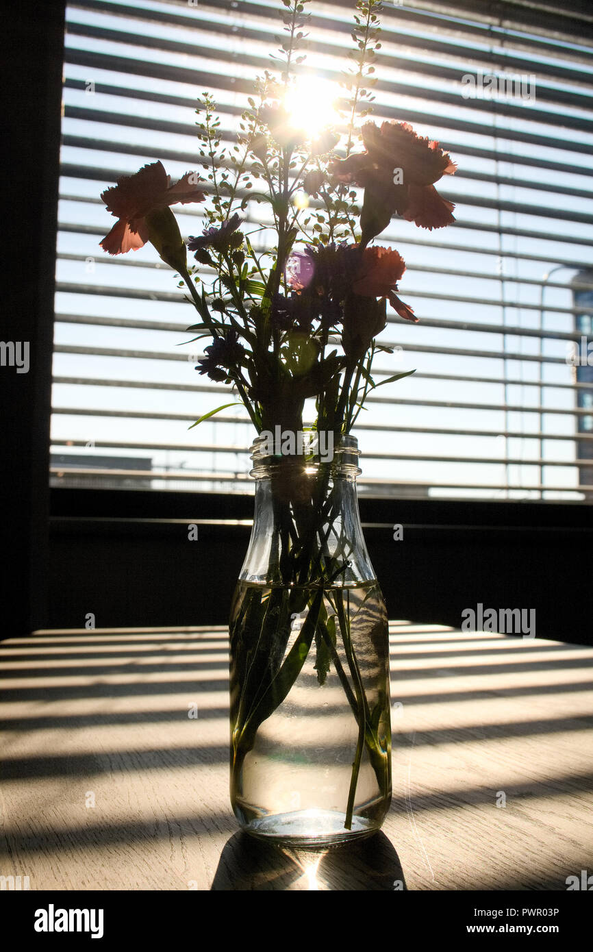 Softly focus of flowers in glass bottle full of water on wooden empty table with horizontal shadows on the table and stunning sunlight coming from a w - Stock Image