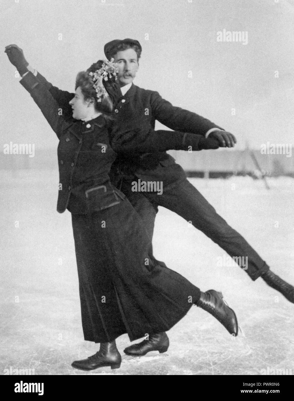 Figure skating at the turn of the century 1800-1900. A couple is pictured together when skating outdoors. - Stock Image