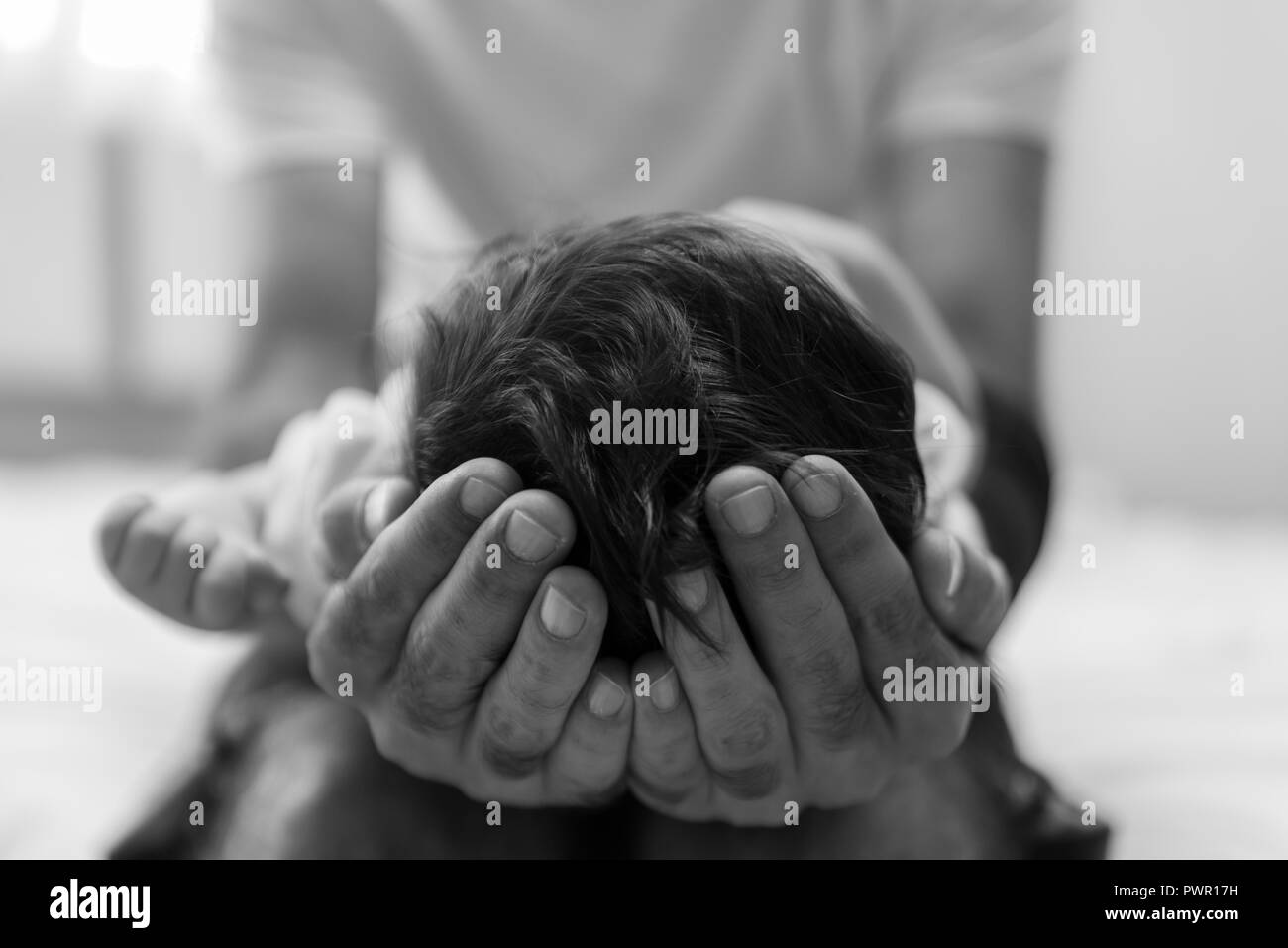 Father is holding the head of his newborn baby in hands, close up. - Stock Image