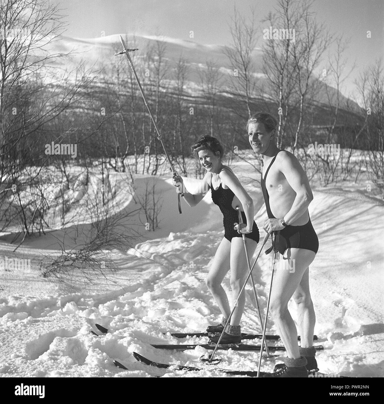 Winter in the 1940s. A young couple is enjoying their winter vacation, and they are wearing their swimsuits to get a nice tan from being outdoors in the warm sun. Sweden 1940s. Photo Kristoffersson Ref D116-1 - Stock Image