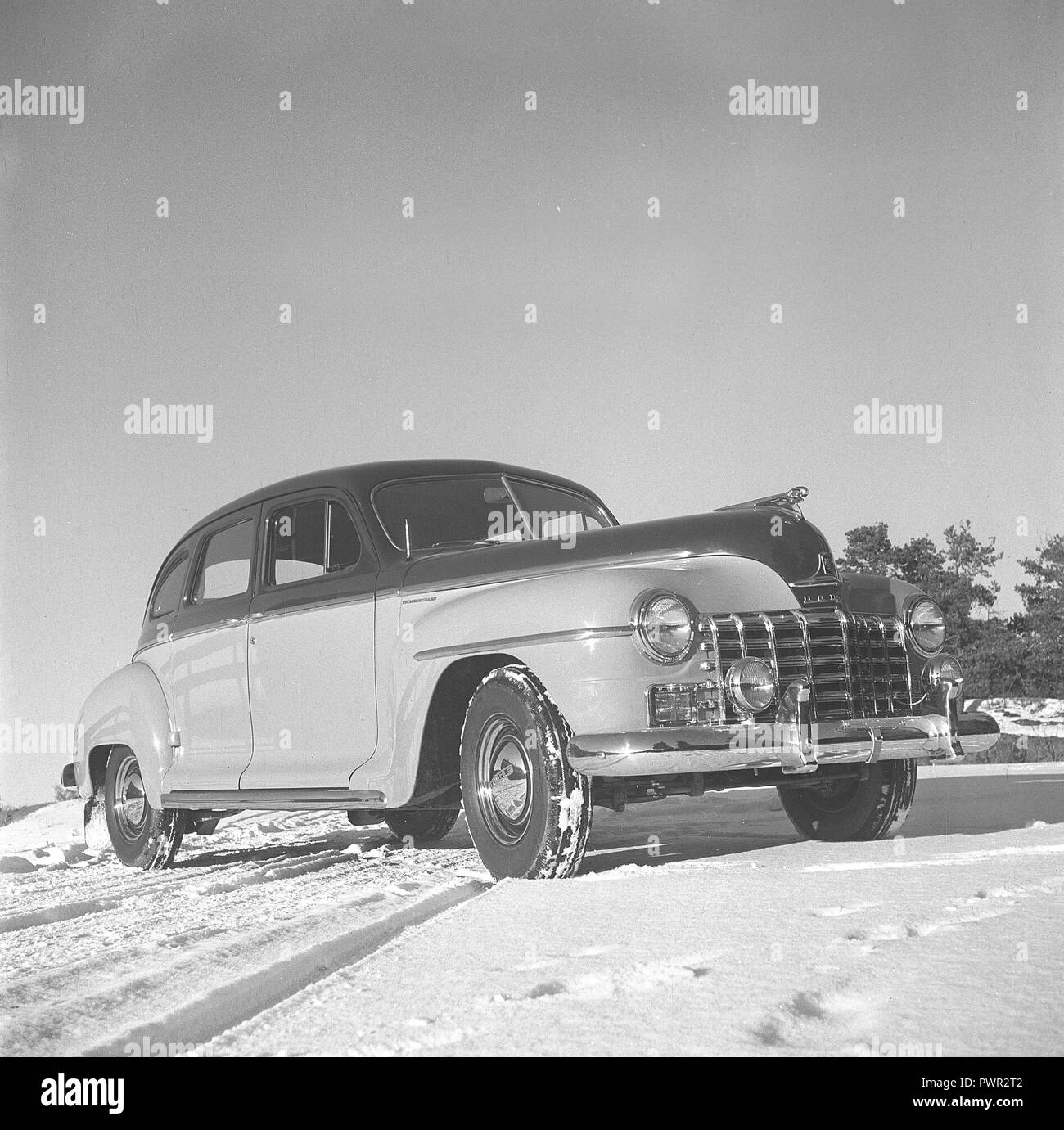 Cars in the 1940s. By the look of it, a brand new american Dodge car, parked in the sun on a winter day. The crome on the fender, grill, lists and hubcaps, sparkles in the sun. Sweden 1940s. Photo Kristoffersson ref AM90-4 - Stock Image