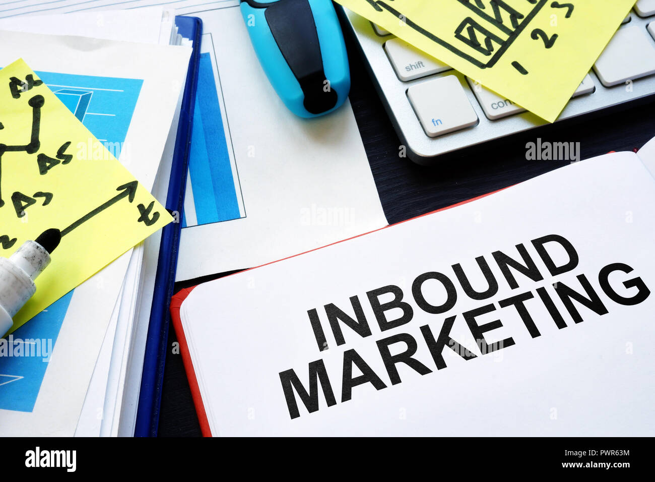 Inbound marketing. Book, reports and pen on table. - Stock Image