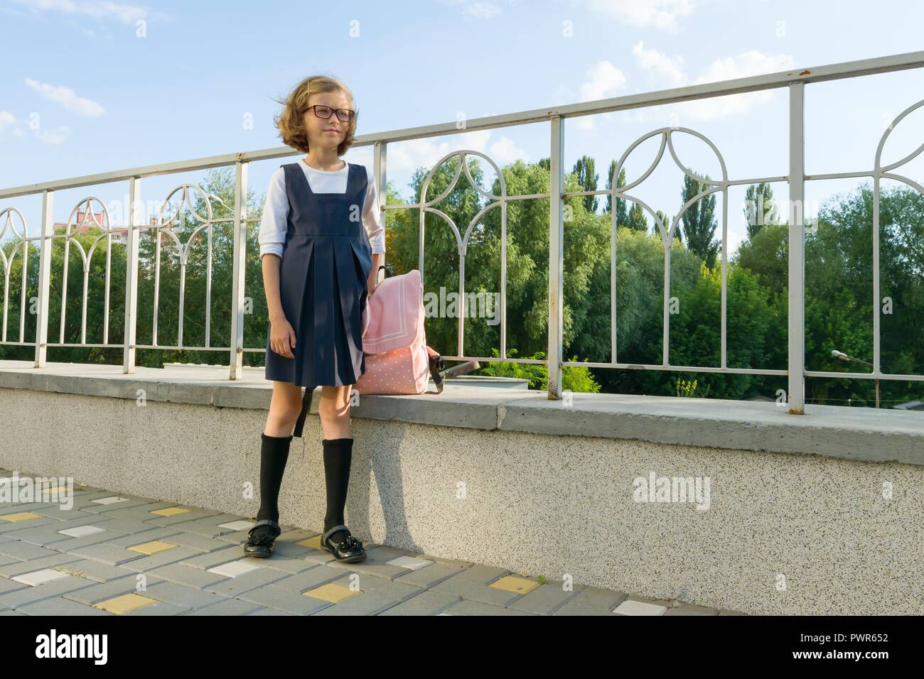 Outdoor portrait of a small student, girl with glasses, uniform with backpack. School, education, knowledge and children, copy space - Stock Image