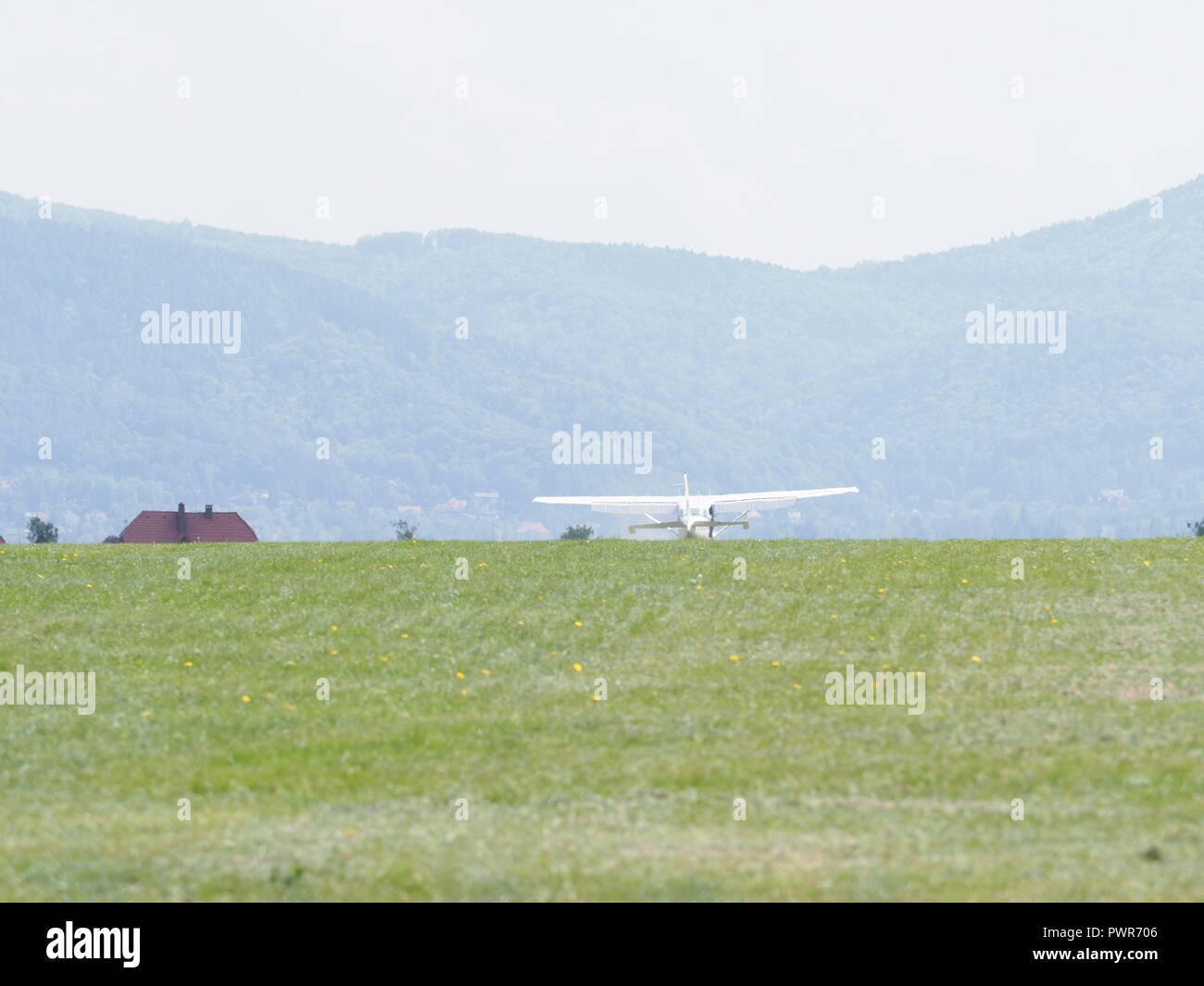 Sport white airplane lands on green grassy airfield landscape in european Bielsko-Biala city at Poland - Stock Image