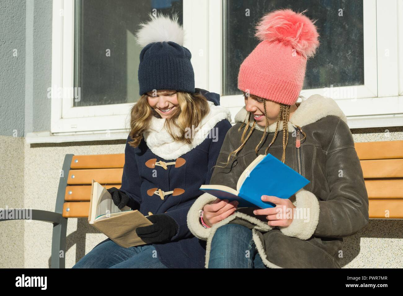 Winter portrait of cheerful young friends students on a bench with books, positive people and friendship concept Stock Photo