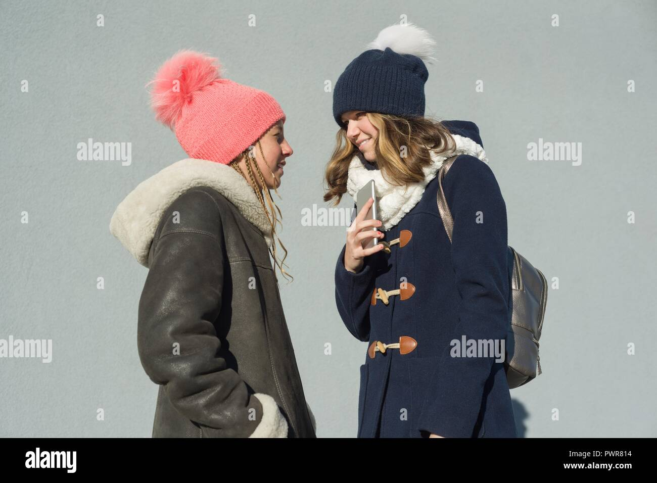 Close-up of an outdoor winter portrait of two teenage girls students in a profile smiling and talking. - Stock Image
