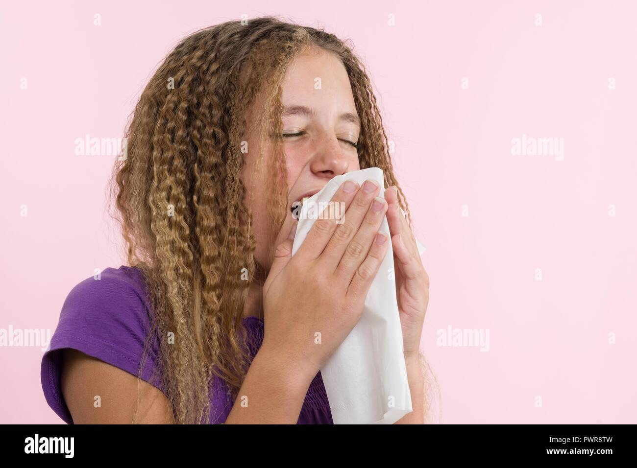 Allergic rhinitis on a summer vacation in a teenage girl's journey. A girl in a T-shirt on a pink background sneezes into a napkin - Stock Image