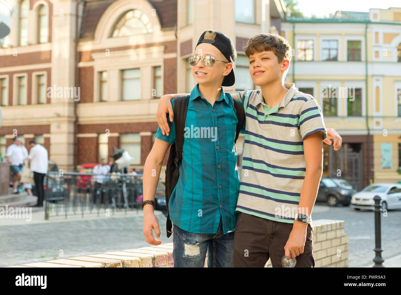 The friendship and communication of two teenage boys is 13, 14 years old, city street background. - Stock Image