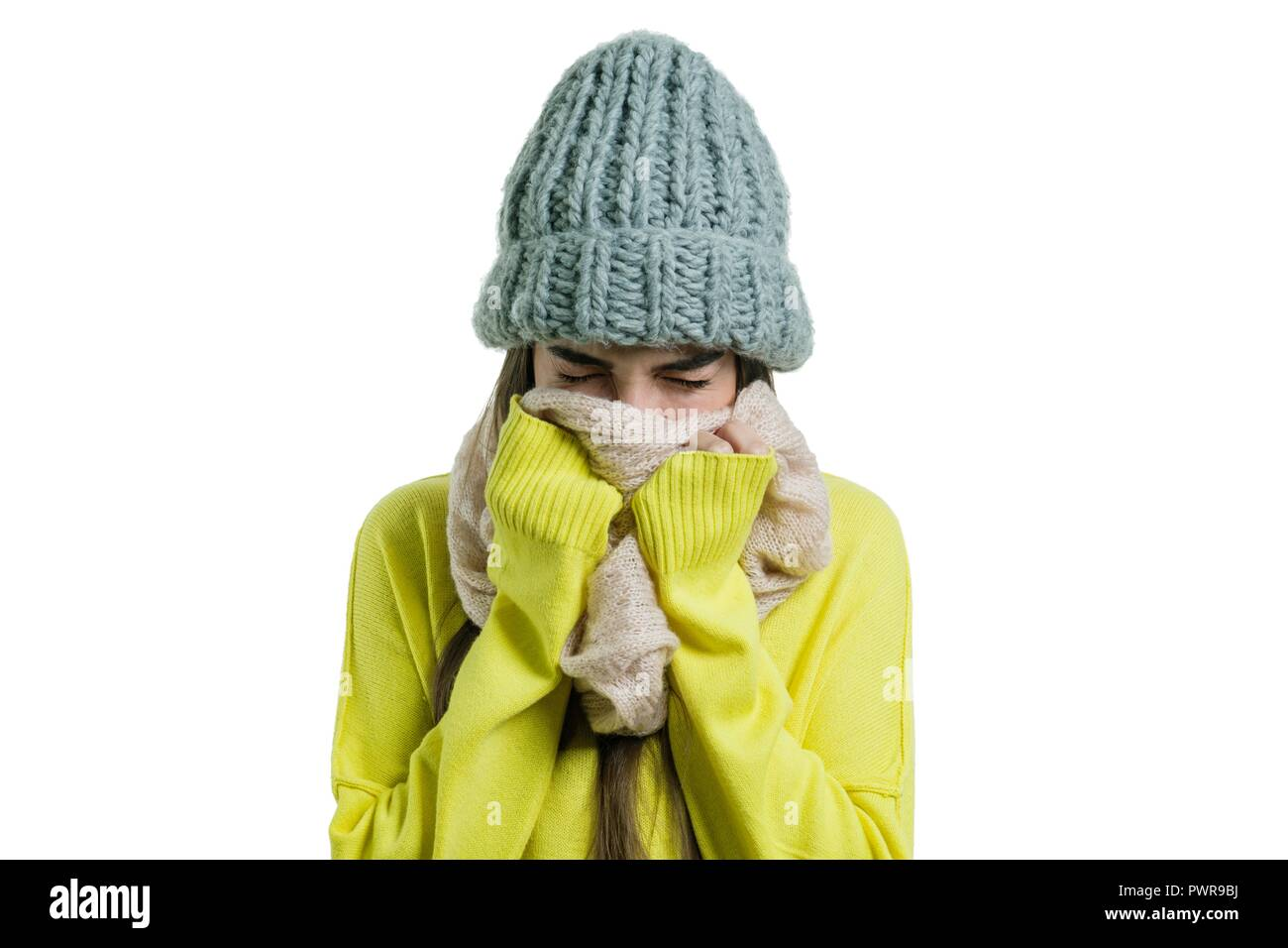 Woman caught a cold, in a knitted cap scarf, sneezes, covered her mouth with her hands. - Stock Image
