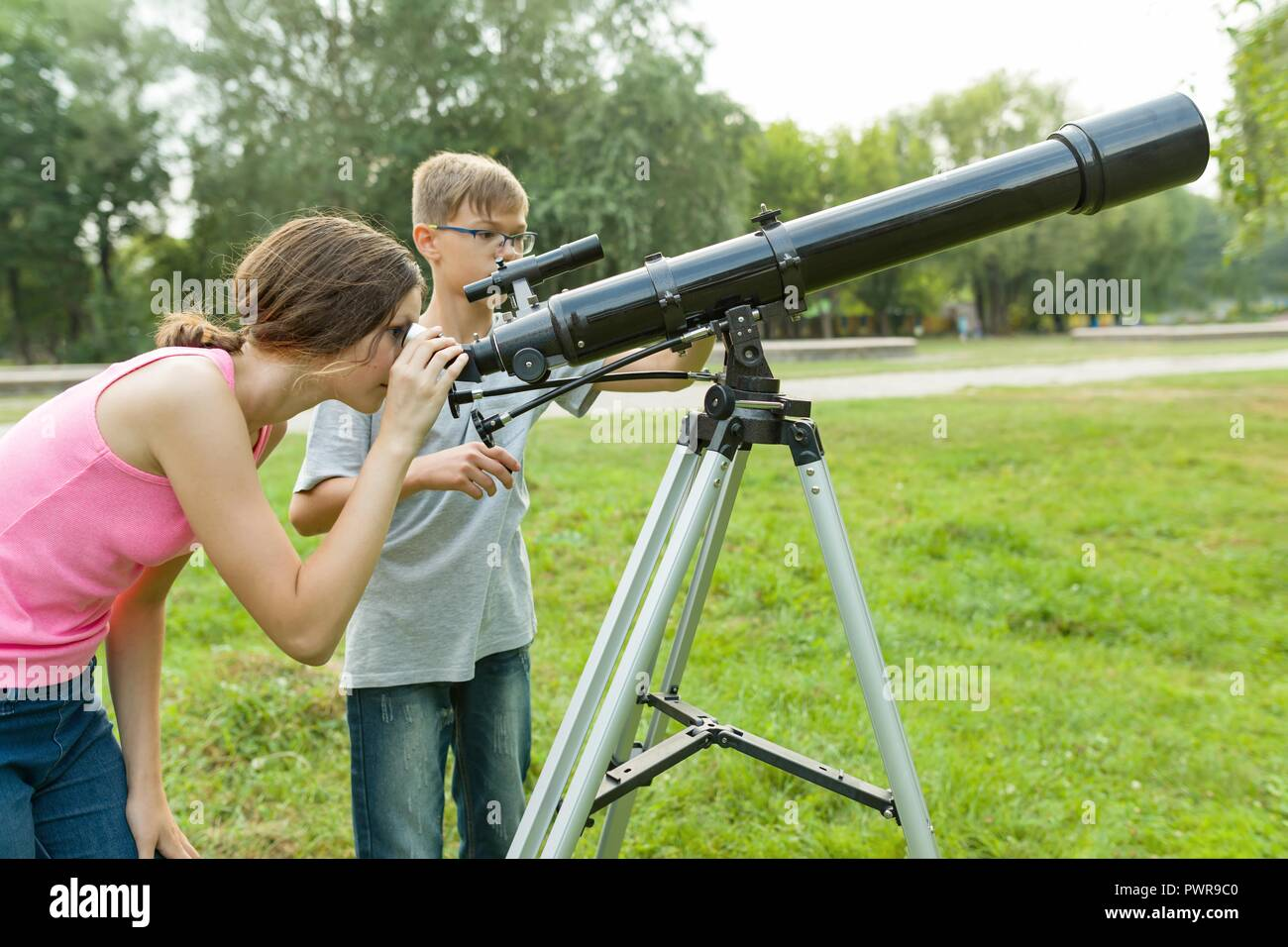 Children teenagers with telescope look at the sky in nature. - Stock Image