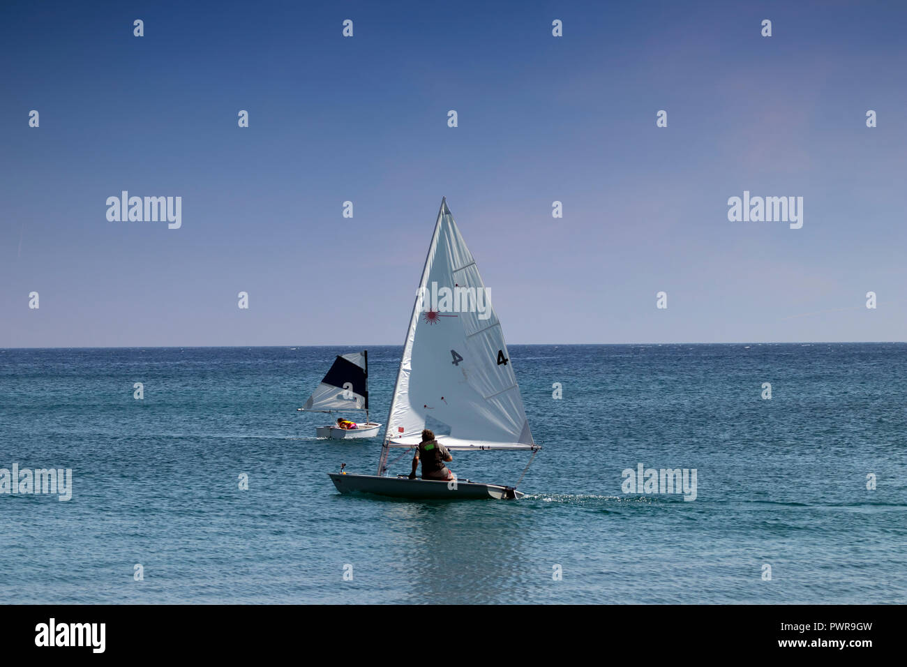 Two small sailboats with one man crew sail the Aegean sea near the shores of Santorini, Greece on a hot summer day. - Stock Image