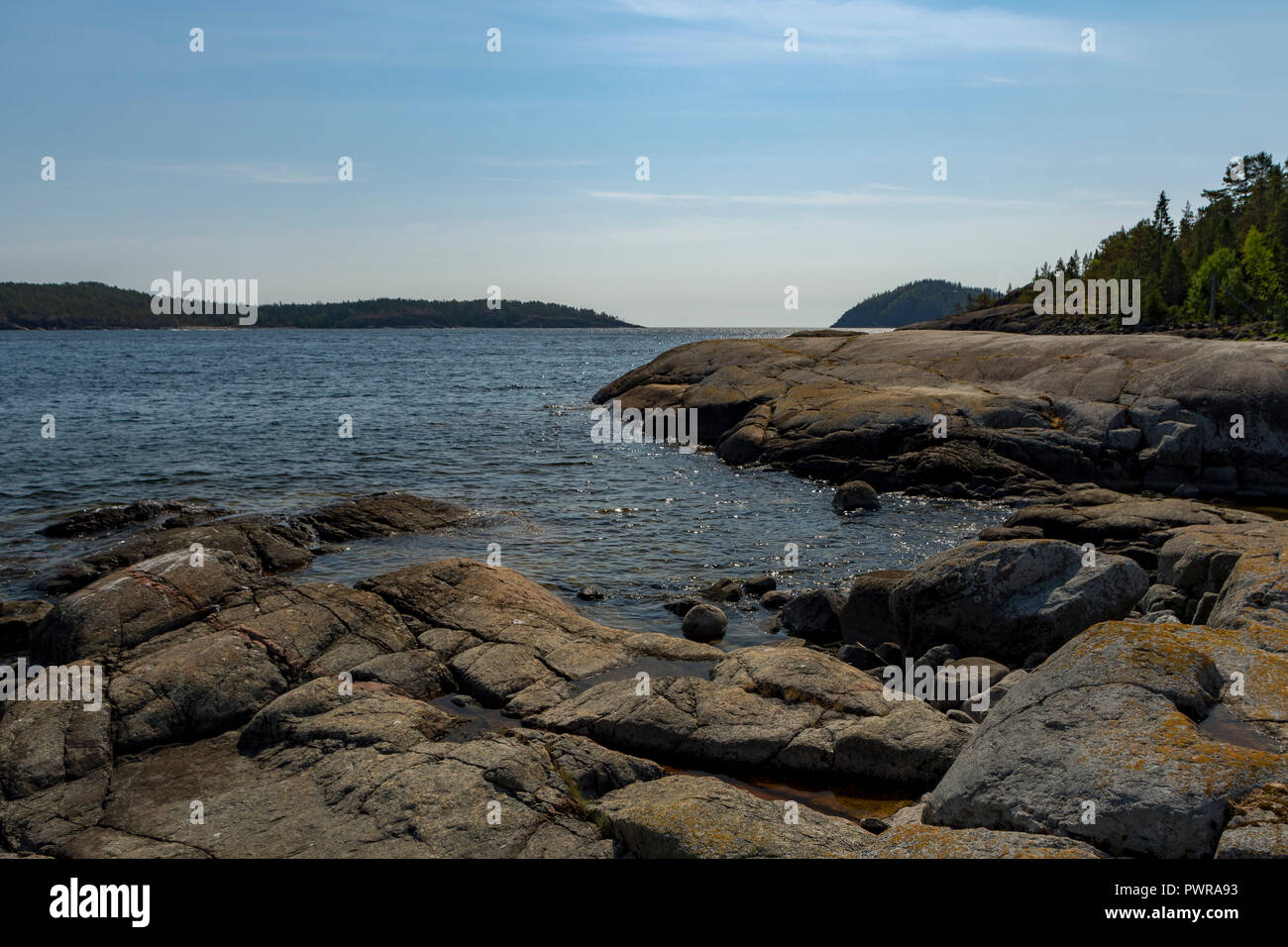 Rocks in seashore in foreground and mountain and blue sky in background, picture from High Coast Area in Northern Sweden. - Stock Image
