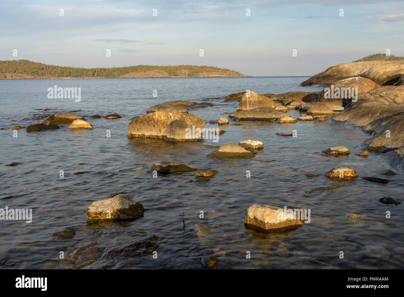 Rocks in seashore in sunset in foreground and mountain with forest and a blue sky in background, picture from High Coast Area in Northern Sweden. - Stock Image