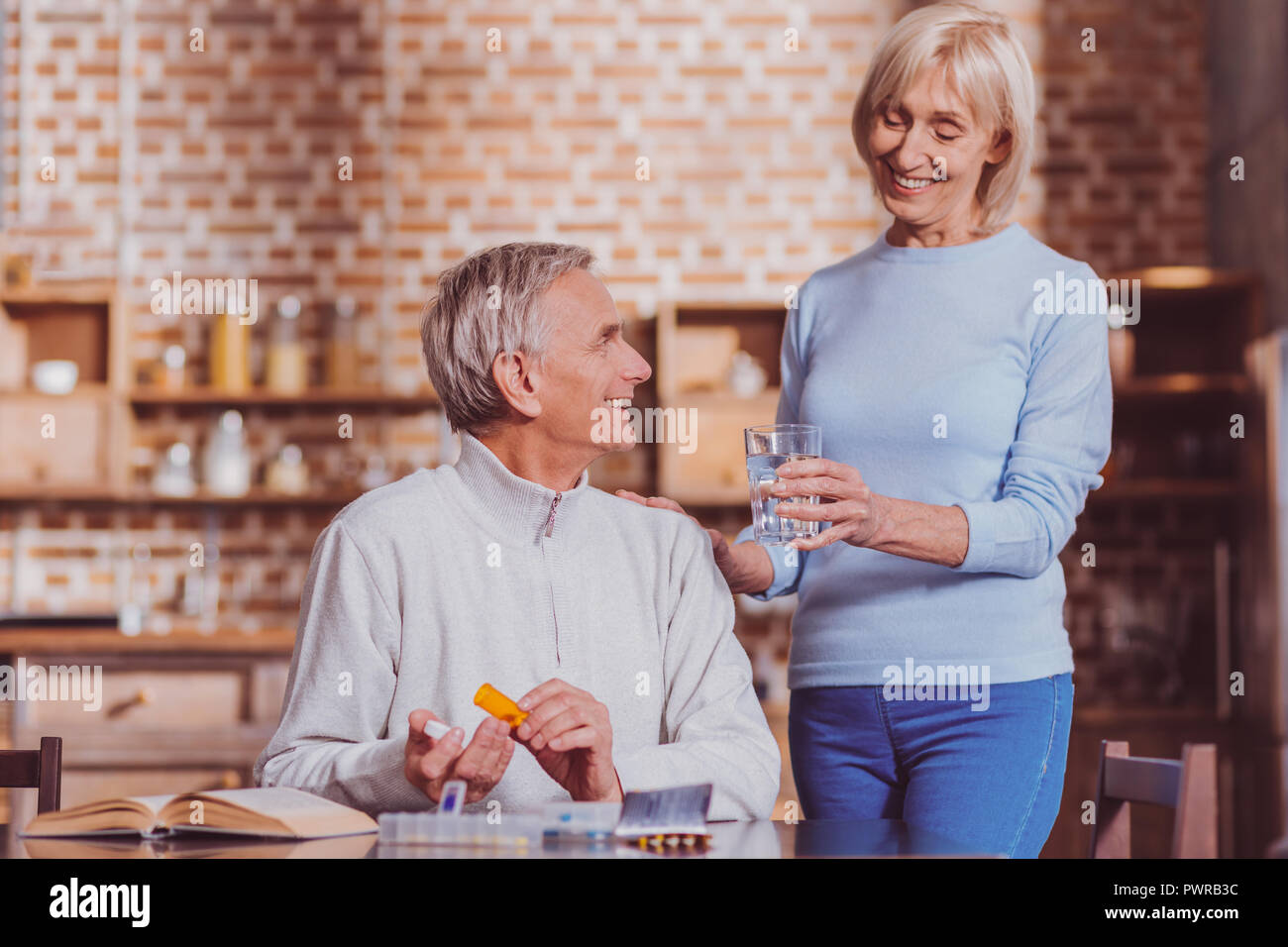 Cheerful wife holding a glass of water - Stock Image