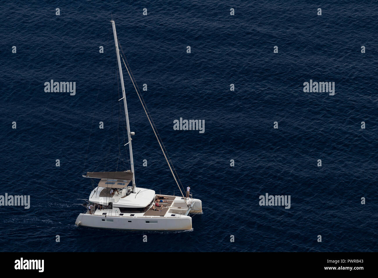 Luxury catamaran yacht sails in the Aegean sea, Greece, August 2018, aerial view. - Stock Image