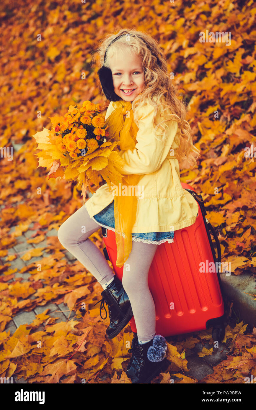 Little girl with blond hair in autumn background - Stock Image