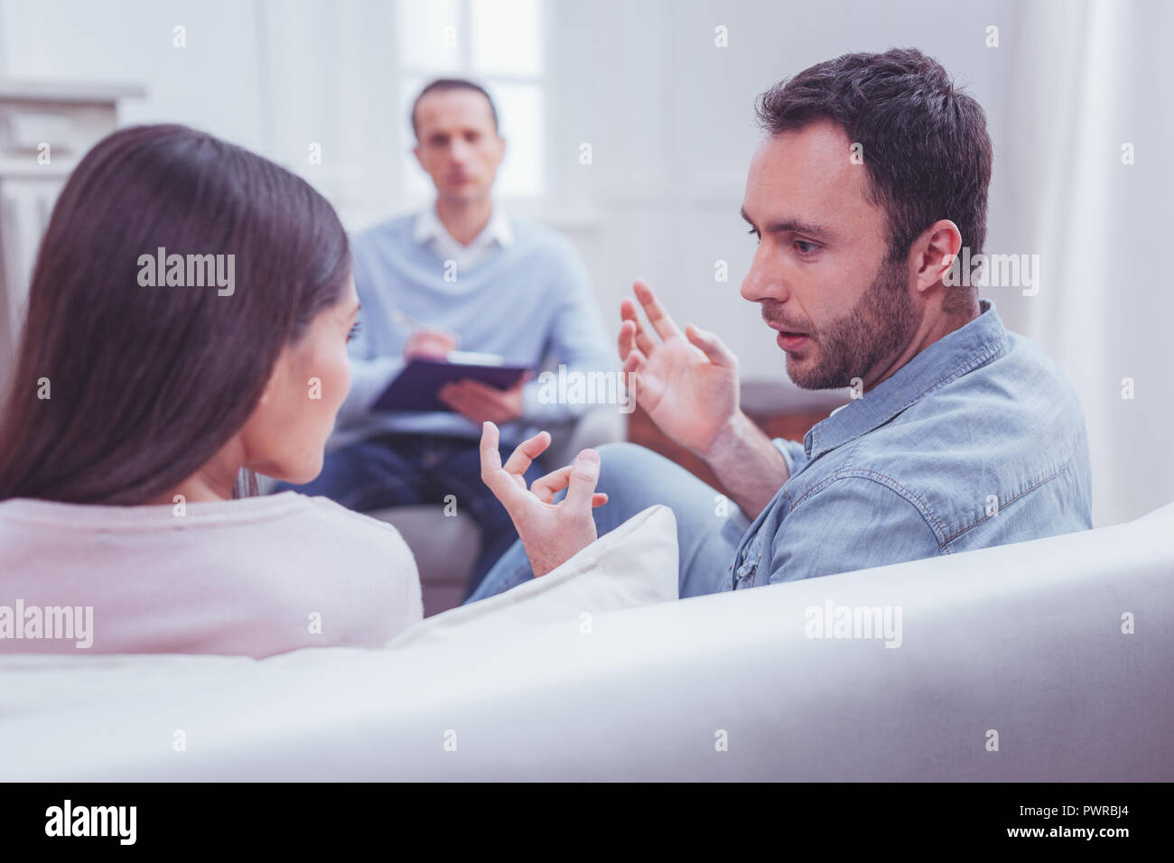 Emotional couple discussing relationships during psychological therapy - Stock Image