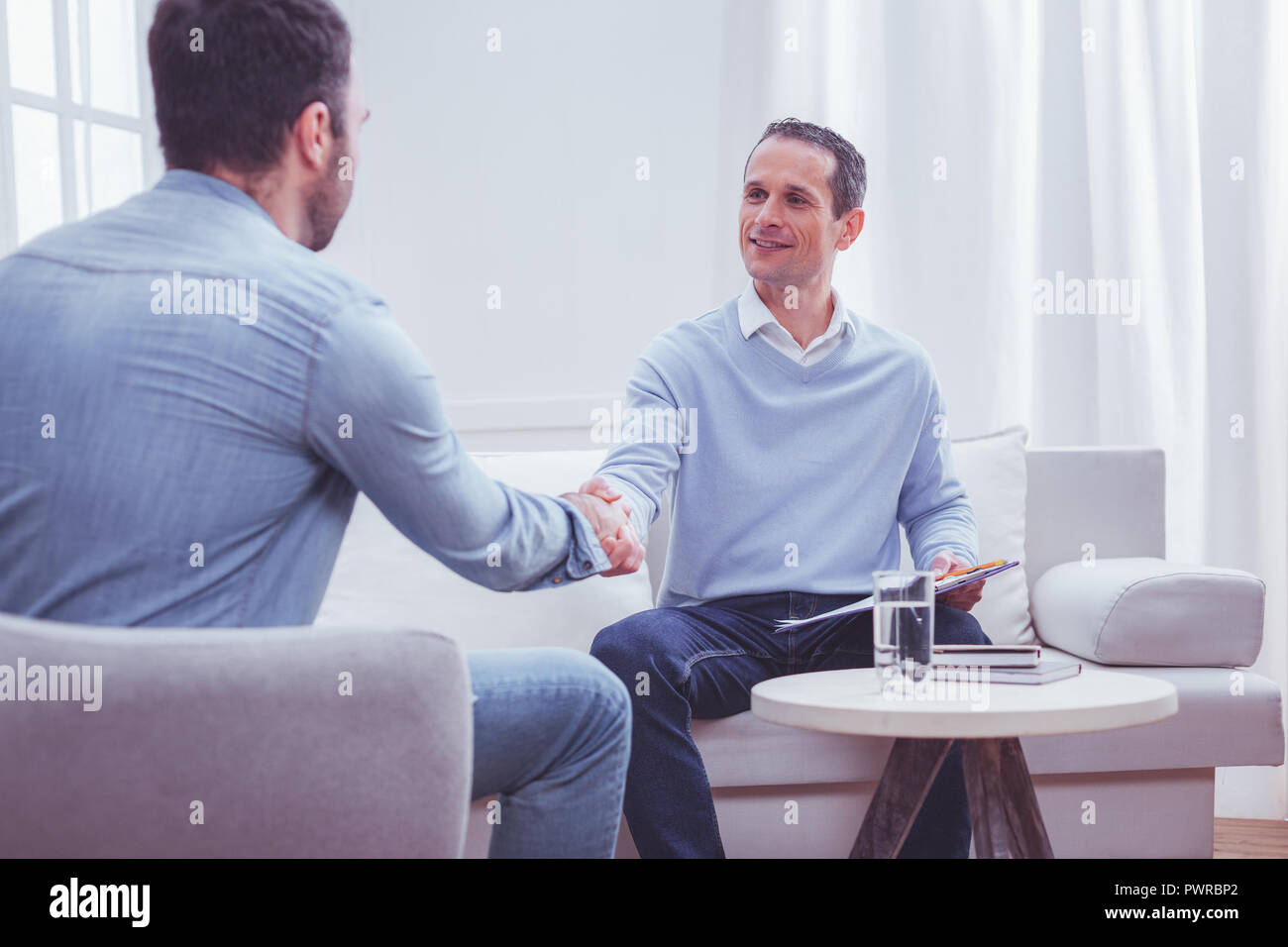 Cheerful psychiatrist saying goodbye to his client - Stock Image