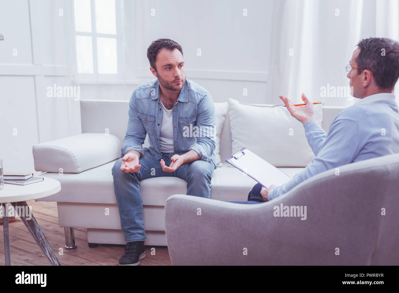 Upset bearded man lifting his hands in dismay during therapy - Stock Image