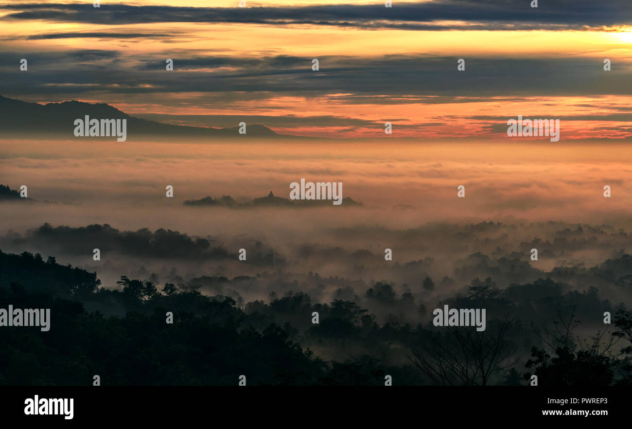 Beautiful sunrise from Setumbu Hills with a view of Mount Merapi Volcano and Borobudur Buddhist Temple (UNESCO World Heritage Site) - Java, Indonesia - Stock Image