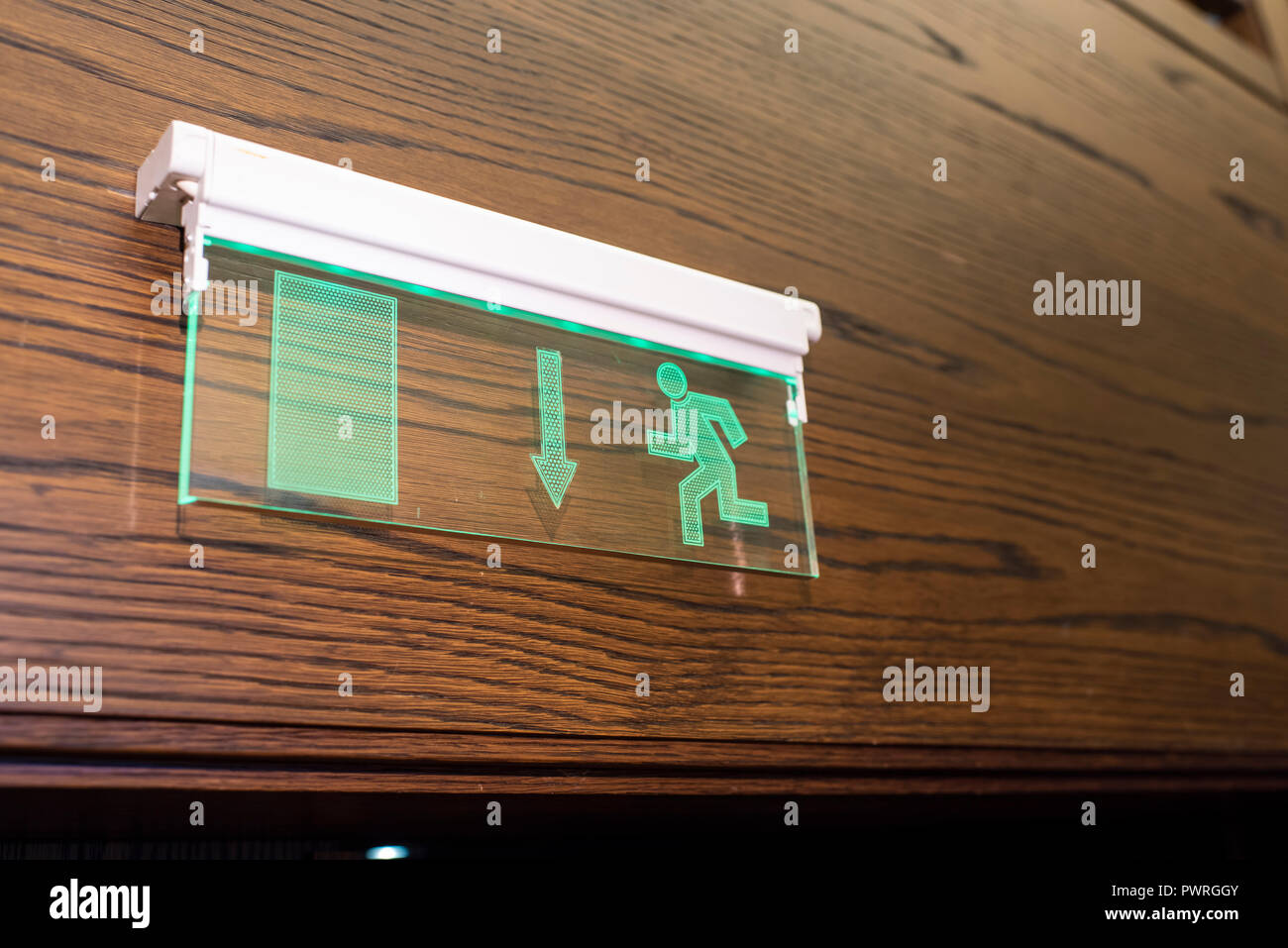 glowing exit sign on the wall Stock Photo