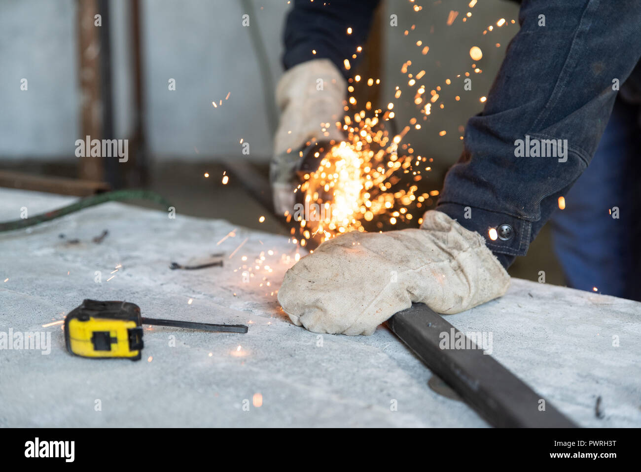Process of cutting metal profile with electric angle grinder. Preparation of parts for welding of metal construction. People at work, profession - Stock Image