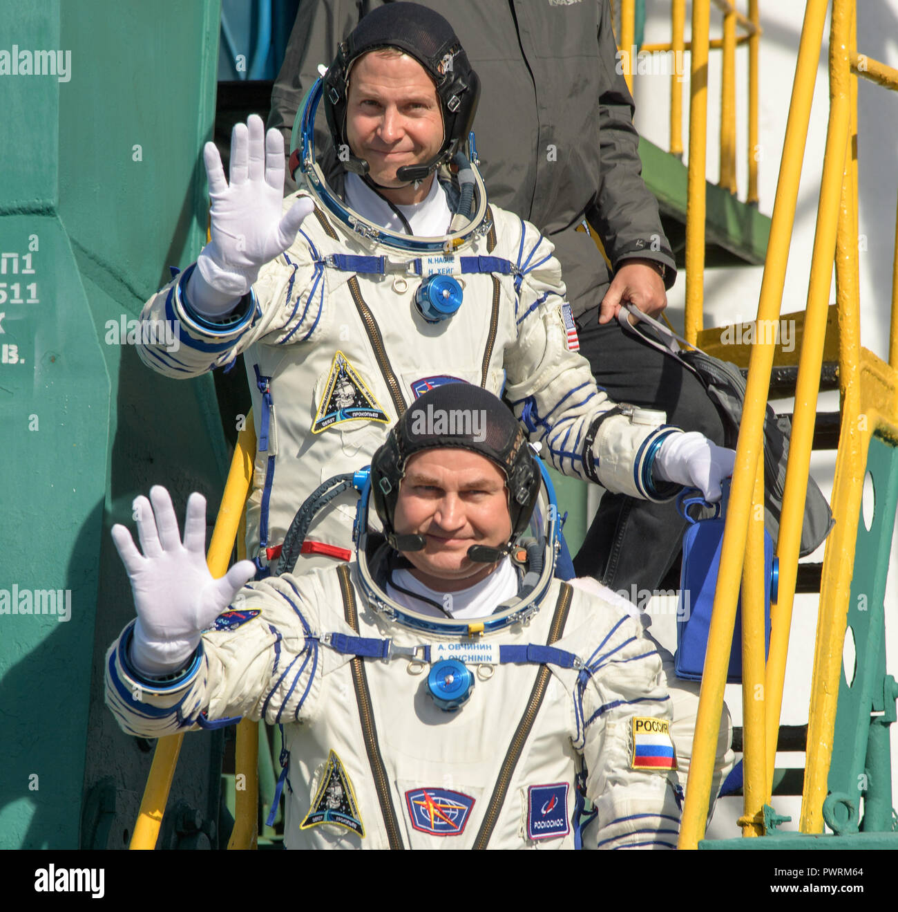 Expedition 57 Flight Engineer Nick Hague of NASA, top, and Flight Engineer Alexey Ovchinin of Roscosmos, wave farewell prior to boarding the Soyuz MS-10 spacecraft for launch, Thursday, Oct. 11, 2018 at the Baikonur Cosmodrome in Kazakhstan. Hague and Ovchinin will spend the next six months living and working aboard the International Space Station. Photo Credit: (NASA/Bill Ingalls) - Stock Image
