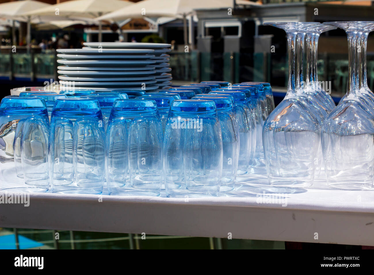 Blue tinted tumblers and wine glasses with plates stacked in a restaurant on the marina in Vilamoura Portugal - Stock Image