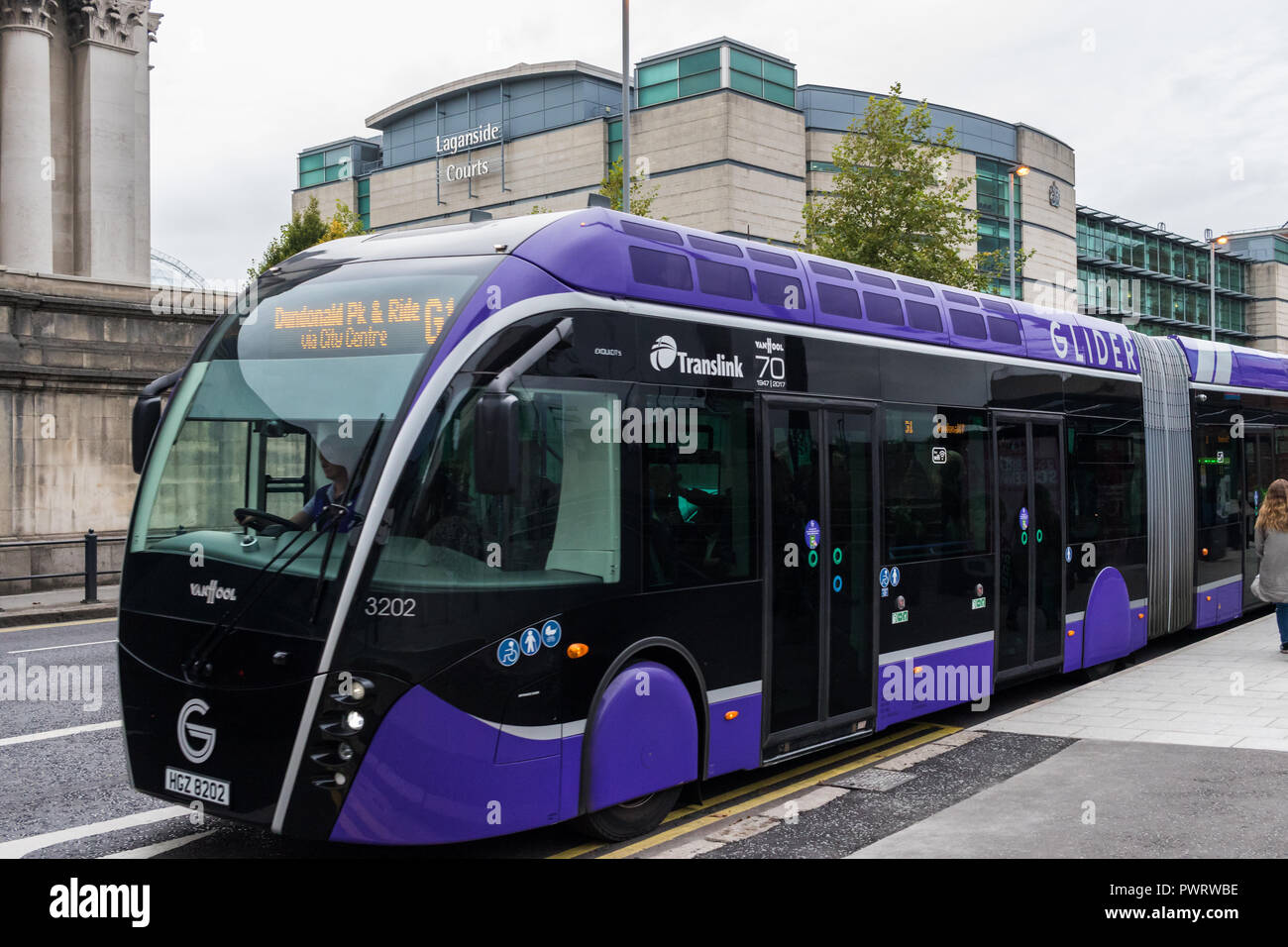 Glider bus pulling away from bus stop with Laganside Courts in background. New articulated buses linking East and West Belfast introduced by Translink - Stock Image