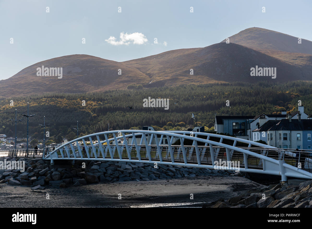 Footbridge over River Shimna connecting promenades with view to Mourne Mountains including Slieve Donard. Newcastle, County Down, N.Ireland. - Stock Image